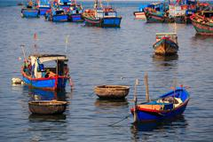 Stock Photo of closeup colourful fishing boats in azure sea against island