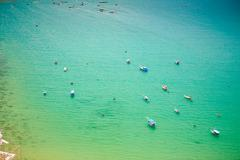 Stock Photo of upper view of fishing tourist boats in azure sea bay