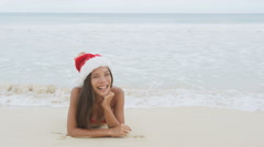 Christmas woman on beach winter vacation wearing santa hat having fun Stock Footage