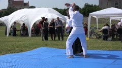 Stock Video Footage of two men demonstrate aikido art element in open air. 4K