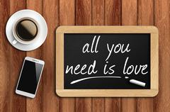 Coffee, phone  and chalkboard with word all you need is love Stock Photos
