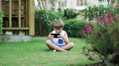 Little Boy With Smartphone Or Tablet Sitting In Garden On Green Grass. Play Game Stock Footage