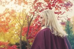 blond woman in a park in autumn - stock photo