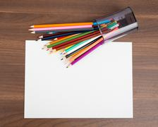 Blank paper with crayons on table Stock Photos
