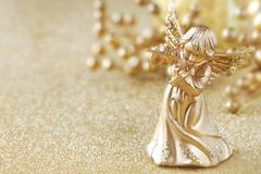 Christmas angel playing a flute with golden decoration at the background Stock Photos