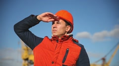 Portrait of a man builder in orange helmet looks into the distance against the - stock footage