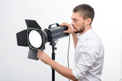 Young male professional photographer is busy fixing the spotlight Stock Photos