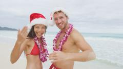 Christmas beach Hawaii couple saying welcome here wearing santa hat and Lei Stock Footage