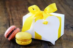 Colourful French macaroons and a gift box with yellow ribbon and an empty hea Stock Photos