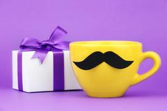 Bright yellow cup with fake ironic hipster mustache and a wrapped gift with p - stock photo