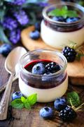 Panna cotta with blueberry and blackberry coulis - Traditional homemade Itali - stock photo