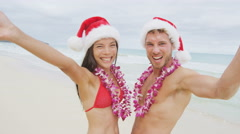 Happy Christmas holiday - couple on Hawaii beach wearing santa hat and Lei Arkistovideo