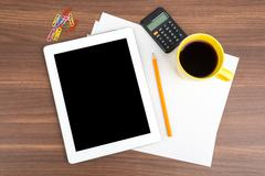 Tablet with blank paper and calculator - stock photo