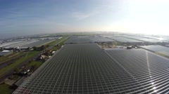 Aerial flying low over large industrial greenhouse showing the glass roofs 4k Stock Footage