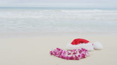 Christmas santa hat and Lei in sand on Hawaii – Christmas travel concept - stock footage