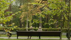 Old women talk on the bench. Autumn daytime. Smooth dolly shot. - stock footage
