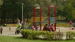 Young mothers with children on playground. Autumn daytime. Smooth dolly shot. Arkistovideo