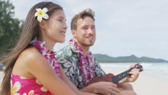 Couple fun on beach playing ukulele on Hawaii having fun romantic time Arkistovideo