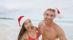 Christmas beach vacation - happy couple cheering having fun Arkistovideo