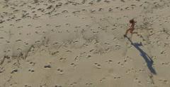 Little boy running on beach drone aerial shot Stock Footage