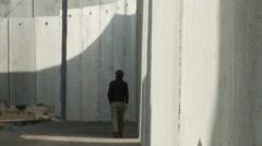 Israeli West Bank Wall - man walks in shadow - stock footage