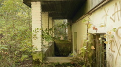 Wall of the deserted factory in the forest. Autumn daytime. Smooth dolly shot. Stock Footage