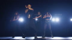 Group of two male and two female are dancing synchronically on a dark stage Stock Footage