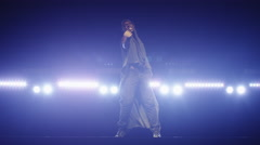 African american male dancer in a hoodie dancing on a dark stage with lights Stock Footage