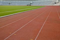 Running track with lawn yard for the athletes background Stock Photos
