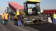 Tracked paver laying fresh asphalt pavement - stock footage