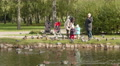 Young family feeds the pigeons and ducks. Autumn daytime. Smooth dolly shot. Footage