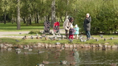 Young family feeds the pigeons and ducks. Autumn daytime. Smooth dolly shot. Stock Footage