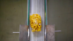 Perpendicular shot of pasta bags on a conveyor belt in a pasta factory. Stock Footage