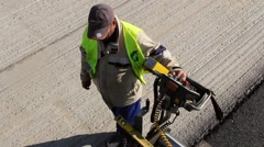 Construction worker operating tracked paver machine - stock footage