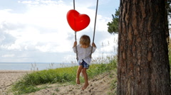 Little boy with balloon swinging on a swing under a tree on the beach Stock Footage