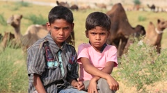 Portrait two young boy and camel involved in Pushkar Camel Mela. India Stock Footage