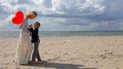 Boy giving red heart balloons to the young woman on the beach. - stock footage