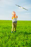 Happy boy playing with toy airplane against blue summer sky and green field - stock photo
