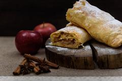 Apple strudel on wooden end of a tree with apples, cinnamon and star anise Stock Photos