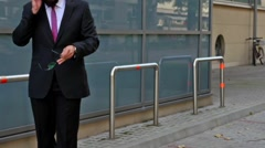 Young businessman outside the office using smartphone. Timelaps Stock Footage