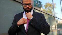 Young attractive businessman ajusting his tie. Outdoor photo Stock Footage