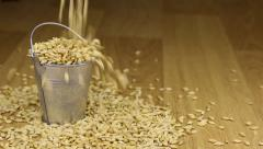 Fall into a bucket of barley grains and on wooden floor Stock Footage
