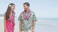 Happy Couple Talking On Hawaiian Beach – Wearing Flowers Lei Walking Stock Footage