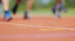 4K Low angle view, the feet of unrecognisable runners on a running track Stock Footage