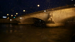 Sailing on a boat along the Seine under a bridge while it's raining, at night. Stock Footage