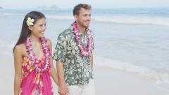 Happy Young Couple Walking On Hawaiian Beach Wearing Flower Lei Stock Footage