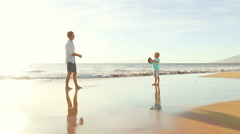 Father and Son Throwing Football Together at the Beach at Sunset. - stock footage