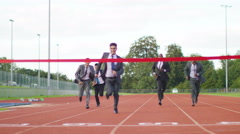 4K Group of competitive businessmen racing to the finish line at running track - stock footage