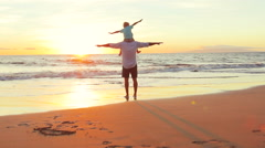 Father and Son Play Airplane Arms Raised Together at the Beach at Sunset. - stock footage