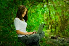 Beautiful young girl using laptop outdoors in the wild enjoying excellent - stock photo